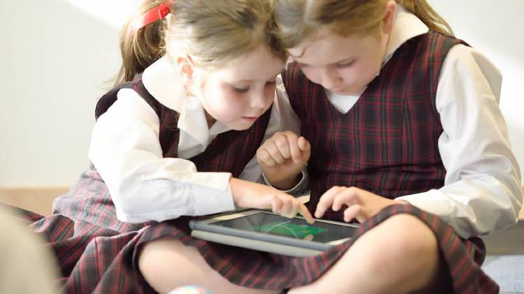Dos niñas estudiando en casa con su tableta