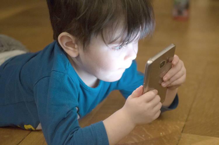 Un niño leyendo desde un móvil pegado a su cara